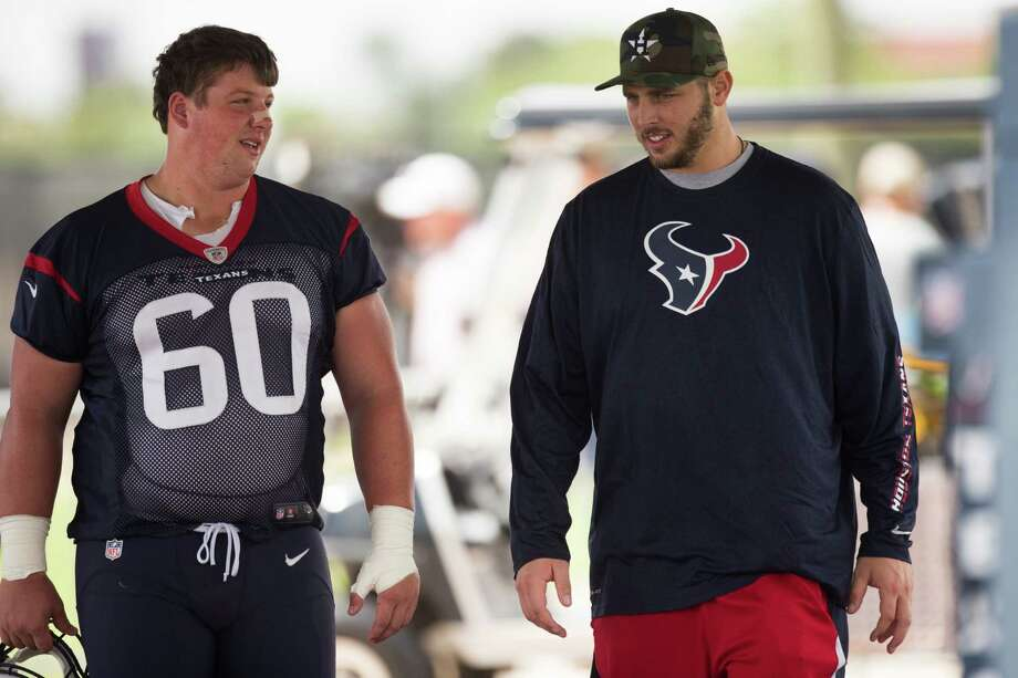 Texans guard Ben Jones (60) talks to tackle David Quessenberry during minicamp Thursday. Quessenberry, who was diagnosed with lymphoma last week, gave a brief speech that Jones said inspired his teammates. Photo: Brett Coomer, Staff / © 2014  Houston Chronicle