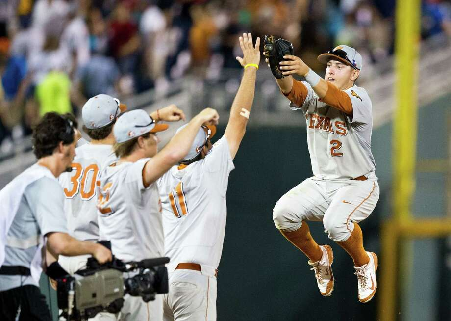 Texas infielder Alex Silver (11) and Mark Payton (2) celebrate the Longhorns' 1-0 victory over UC Irvine on Wednesday. Photo: Chris Machian / Omaha World-Herald / OMAHA WORLD-HERALD