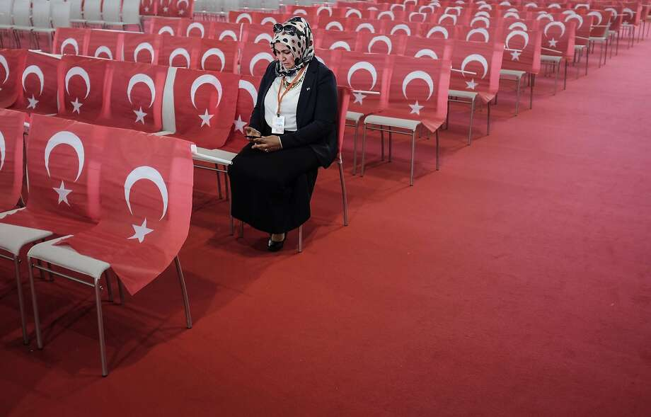 """TOPSHOTS A woman wearing a head scarf checks her mobile device as she awaits the speech of the Turkish Prime Minister during an event to mark the 10th anniversary of the Union of European Turkish Democrats UETD at the Albert Schultz Hall in Vienna, Austria on June 19, 2014. Austria warned the Turkish Prime Minister on June 12, 2014 not to say anything that may """"split"""" Austrian society during his visit.   AFP PHOTO / PATRICK DOMINGOPatrick Domingo/AFP/Getty Images Photo: Patrick Domingo, AFP/Getty Images"""