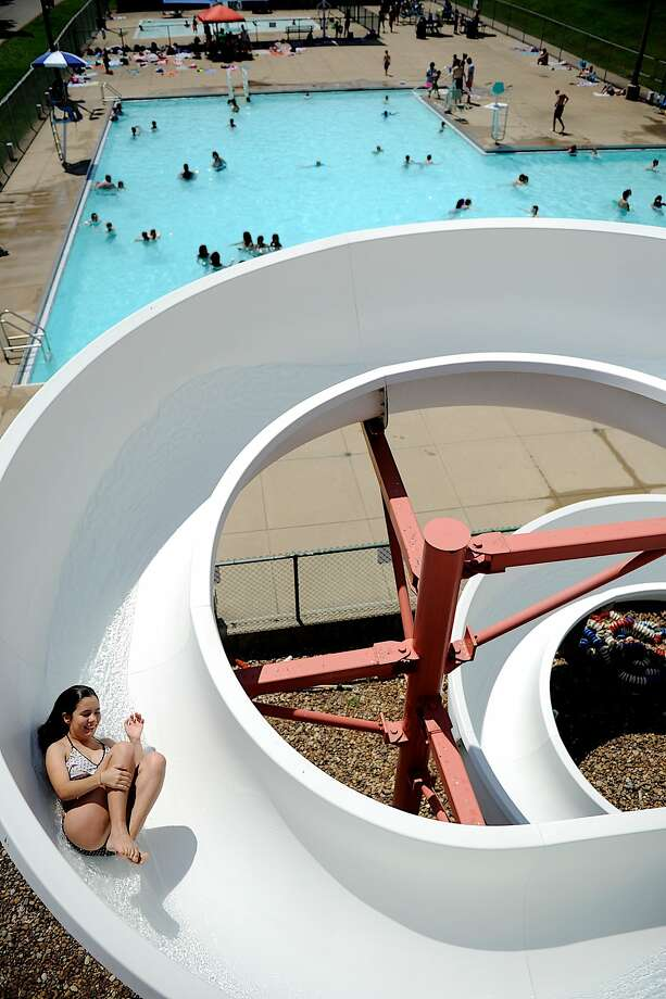 Carly Davidson, 14, zips down the slide at Atkinson Pool in Henderson, Ky. on a hot Thursday afternoon, June 19, 2014. (AP Photo/The Gleaner, Darrin Phegley) Photo: Darrin Phegley, Associated Press