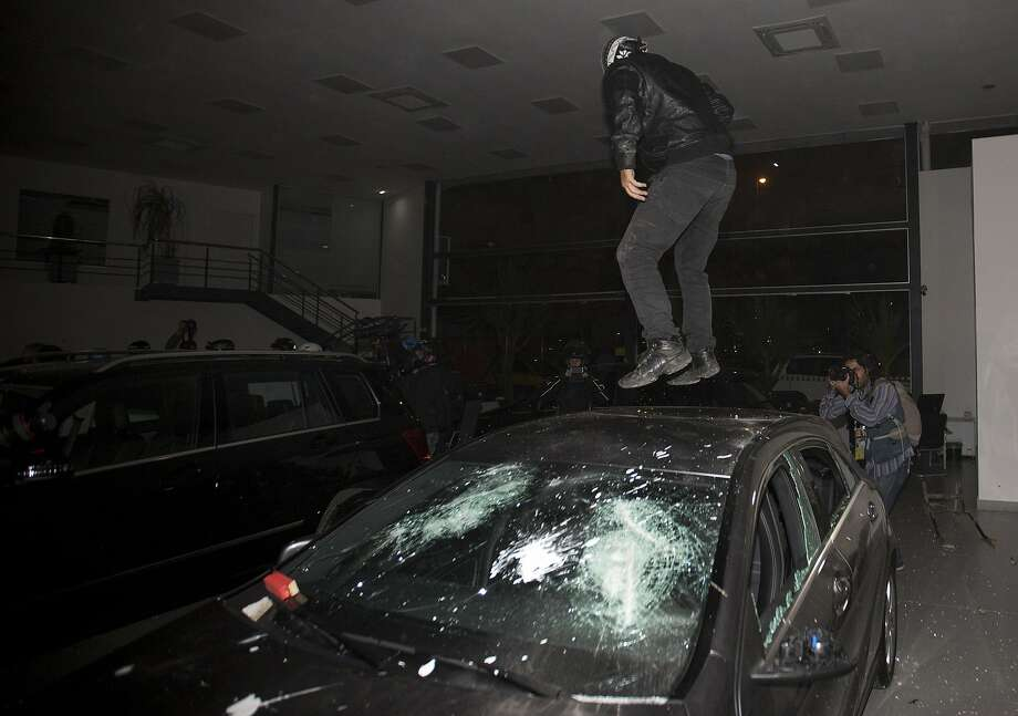 A masked demonstrator jumps on the roof of a trashed luxury car at a dealership, after a protest march in Sao Paulo, Brazil, Thursday, June 19, 2014. Protesters smashed the windows of luxury cars inside a dealership, trashed banks and fired powerful fireworks at police during a demonstration that drew about 2,000 Thursday as Sao Paulo, Brazil's biggest city, hosted a World Cup match.  (AP Photo/Eduardo Verdugo) Photo: Eduardo Verdugo, Associated Press