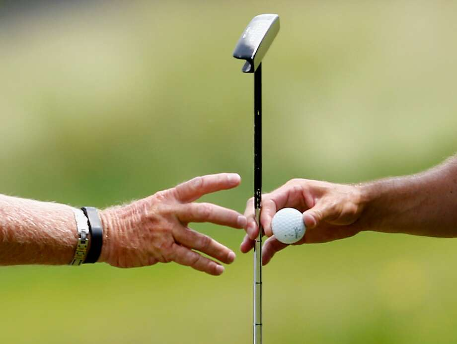 CROMWELL, CT - JUNE 19: Zach Johnson (R) of the United States hands his putter and golf ball to his caddie Damon Green (L) during the first round of the Travelers Championship golf tournament at the TPC River Highlands on June 19, 2014 in Cromwell, Connecticut.  (Photo by Jim Rogash/Getty Images) Photo: Jim Rogash, Getty Images