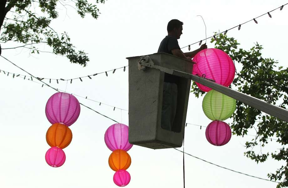 Jared Brown, who works for the Fairmount Park Commission, begins the process of hanging more than 100 colorful lanterns on the lights strung through the trees of Philadelphia's Eakins Oval Park on Thursday, June 19, 2014. (AP Photo/The Philadelphia Inquirer, Michael Bryant) Photo: Michael Bryant, Associated Press