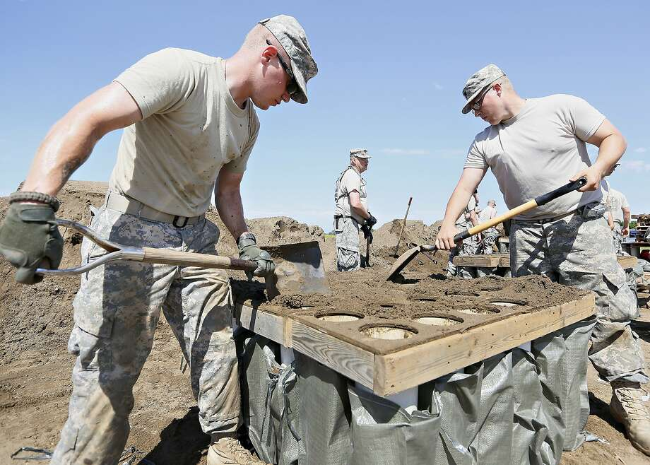 National Guardsmen Spc. Korey Relph, left, of Sioux Falls, and Spc. Joshua Driver, right, of Yankton, fill sandbags at Dakota Valley Elementary School as residents prepare for flooding in McCook Lake, S.D., on Thursday, June 19, 2014. People along the river were working to battle record flooding. (AP Photo/Sioux City Journal, Dawn J. Sagert) Photo: Dawn J. Sagert, Associated Press