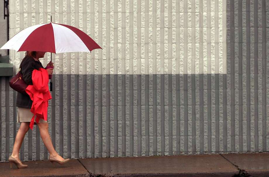 A woman uses an umbrella to keep from getting wet as she walks in the rain along North Wyoming Street in Hazleton, Pa, on Thursday, June 19, 2014. (AP Photo/Hazleton Standard-Speaker, Ellen F. O'Connell) Photo: Ellen F. O'Connell, Associated Press