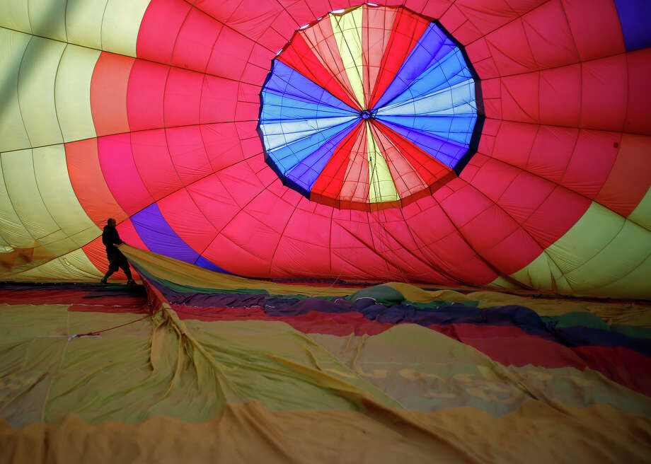 Balloon pilot Todd Monahan of Glens Falls walks inside his balloon, spreading out the envelope to ensure maximum airflow upon liftoff, Friday morning, June 20, 2014, at the Saratoga County Fairgrounds in Ballston Spa, N.Y. (Tom Brenner/ Special to the Times Union) Photo: Tom Brenner / ©Tom Brenner/ Albany Times Union