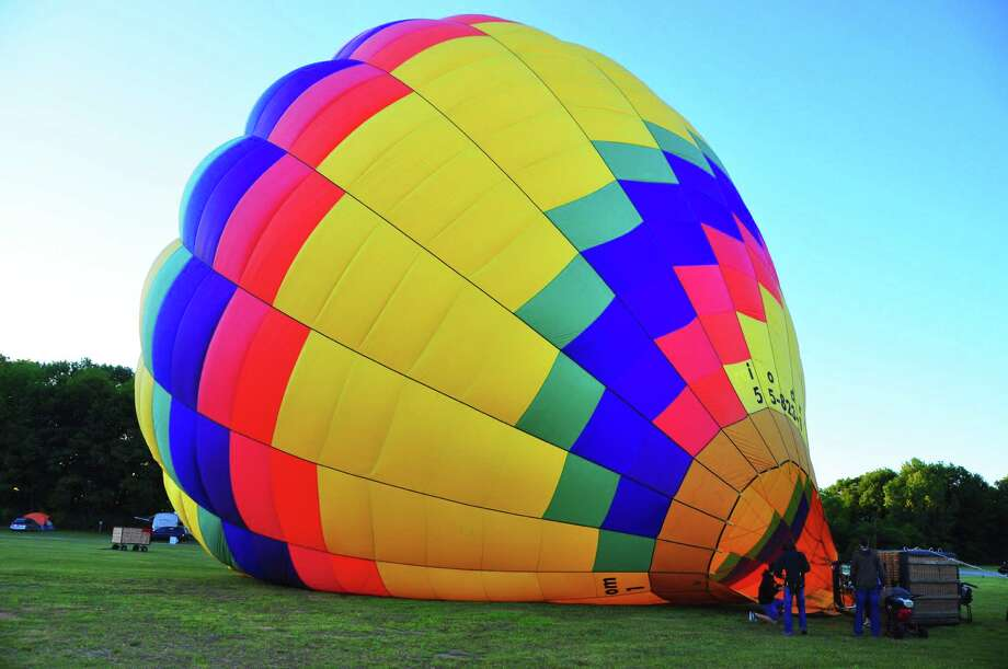 A balloon from SunKiss Ballooning is inflated early Friday, June 20, 2014,  at the Saratoga County Fairgrounds in prepartion for the first Saratoga Balloon & Craft Festival, running Friday through Sunday, June 20 to 22. (Photo by Steve Barnes/Times Union)
