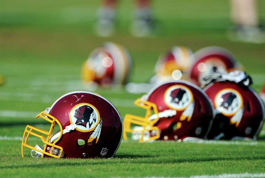 "FILE - In this June 17, 2014, file photo, Washington Redskins helmets sit on the field during an NFL football minicamp in Ashburn, Va. The U.S. Patent Office ruled Wednesday, June 18, 2014, that the Washington Redskins nickname is ""disparaging of Native Americans"" and that the team's federal trademarks for the name must be canceled. The ruling comes after a campaign to change the name has gained momentum over the past year. (AP Photo/Nick Wass, File) Photo: Nick Wass, Associated Press / FR67404 AP"