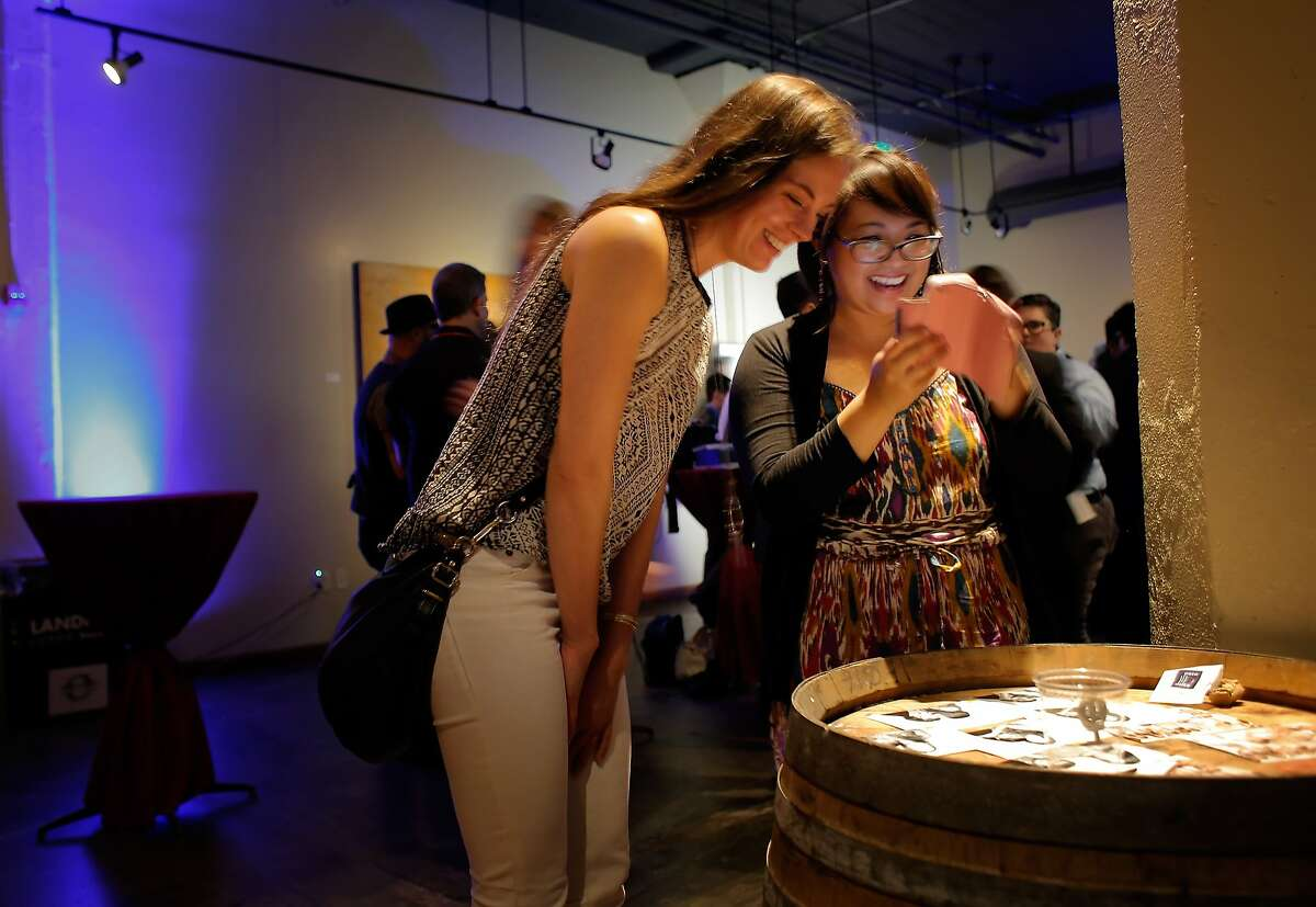 Kristina Willemse, left, and Giovannie Espiritu, right, look over pictures of themselves at the Frameline Film Festival opening night party on Thursday, June 19, 2014, in San Francisco, Calif., where celebrities, filmmakers and subjects of,