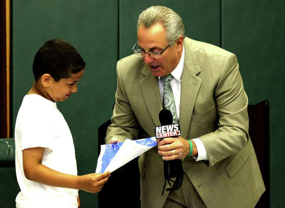 "El-Shareem Daniels, 9. talks about his drawing with Troy Mayor Lou Rosamilia on Friday morning, June 20, 2014, at Carroll Hill School in Troy N.Y. Rosamilia was given 21 books made by 650 Troy City School District students titled ""Describe Your City."" (Selby Smith / Special to the Times Union) Photo: Selby Smith / 00027424A"