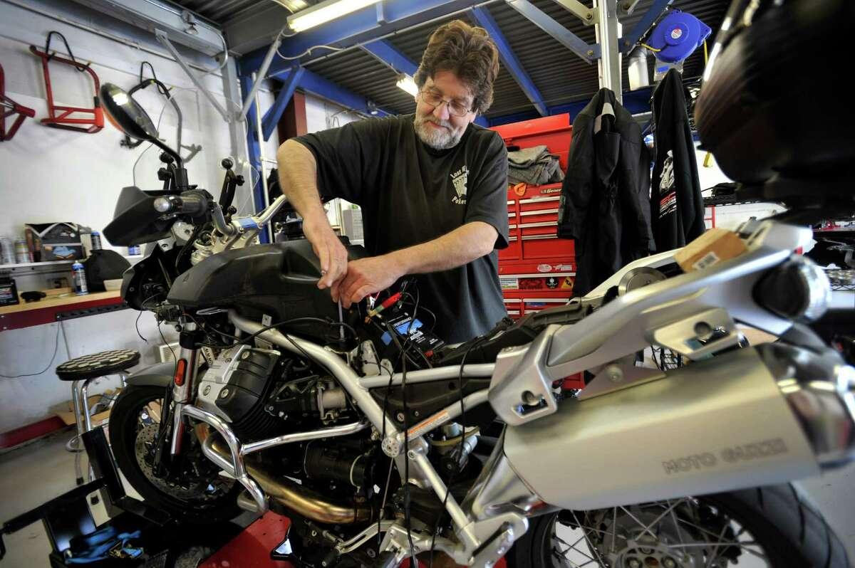 Mechanic Jeff Ciurek, 59, of Redding, Conn.works on a Moto Guzzi Stelvio motorcycle at of Hamlin Cycles, 44 Grassy Plain Rd. in Bethel, Conn., Friday, June 20, 2014.