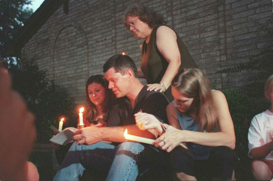 Kathy Crisp rests a hand on Russell Yates' shoulder during this candlelight vigil held in front of the Yates' home in Clear Lake Friday June 22, 2001, where their 5 children were murdered earlier this week. The mother is held on murder charges.     HOUCHRON CAPTION (06/23/2001):  Kathy Crisp, standing, the aunt of Russell Yates, center, joins family members and friends in a candlelight vigil Friday in front of the Yates home in Clear Lake. Photo: Andrew Innerarity, Houston Chronicle / Houston Chronicle