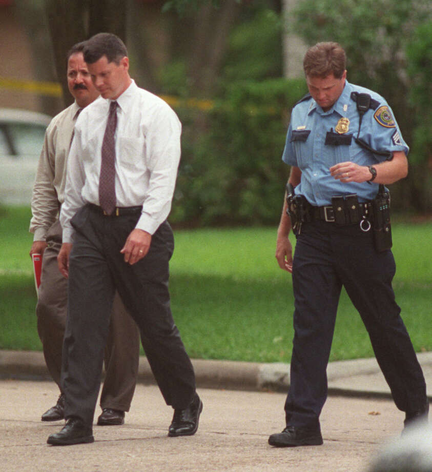 Father of the five slain children, Russell E. Yates, is escorted back to his house by police. His wife, Andrea Pia Yates, was charged late Wednesday with capital murder-multiple counts. Photo: Steve Campbell, Houston Chronicle / Houston Chronicle
