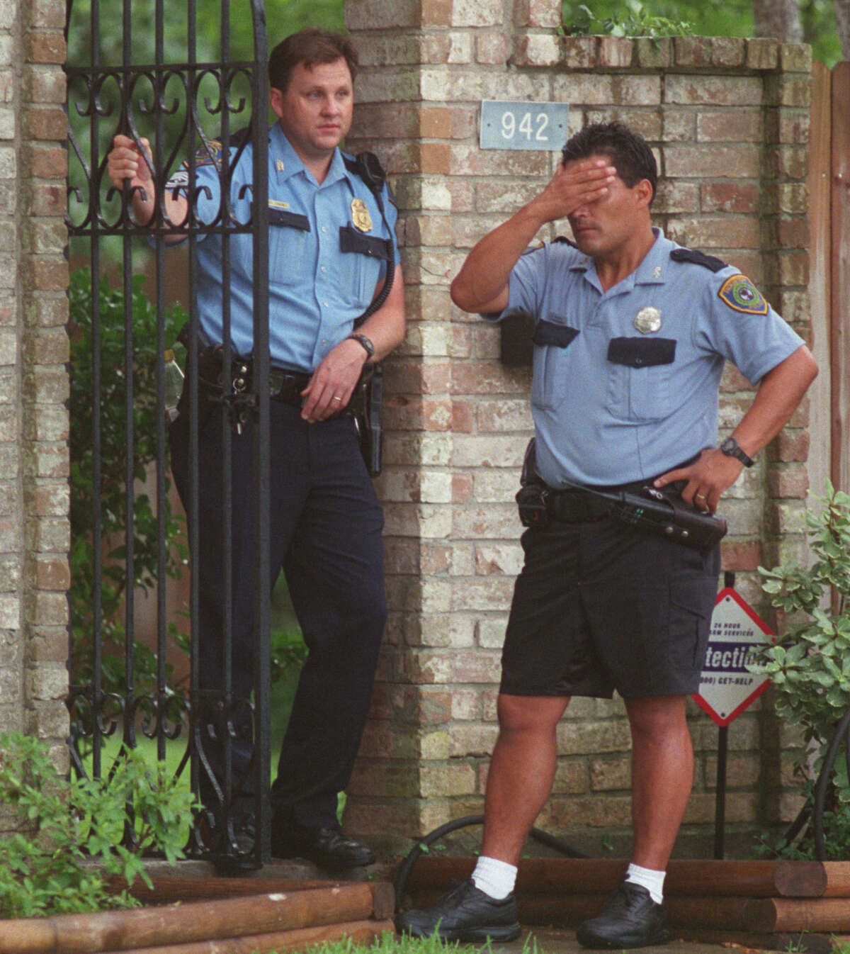 Houston police officers stand outside the house where five children were found dead in Clear Lake on Wednesday, June 20, 2001. The mother, Andrea Pia Yates, was said to be on medication for depression and was arrested and charged with five counts of capital murder.