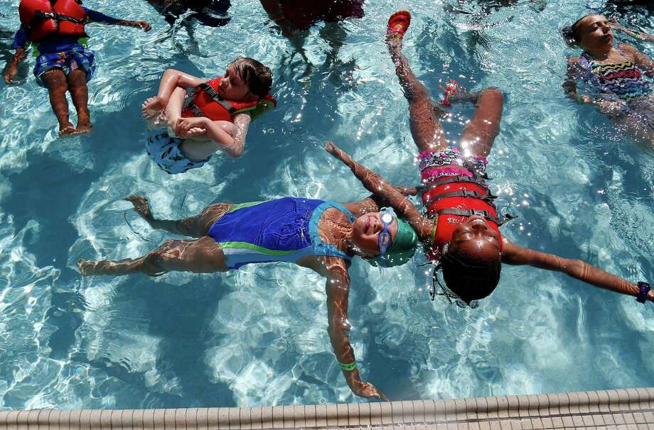 Hanna Rosanes, left, and Tiana Guyton, right float together during the 2014 World's Largest Swim Lesson at the University of Houston's Campus Recreation and Wellness Center, Friday, June 20, 2014, in Houston. Photo: Karen Warren, Houston Chronicle / © 2014 Houston Chronicle