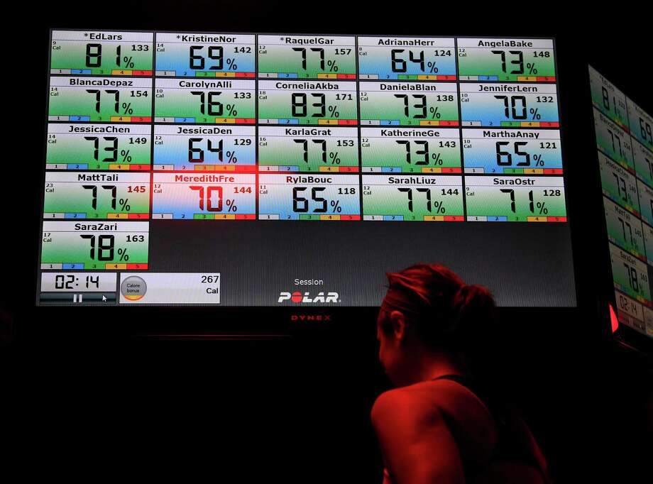 A video monitor displays a constant reading of workout participants' heart rates during a session. Photo: Karen Warren, Staff / © 2014 Houston Chronicle