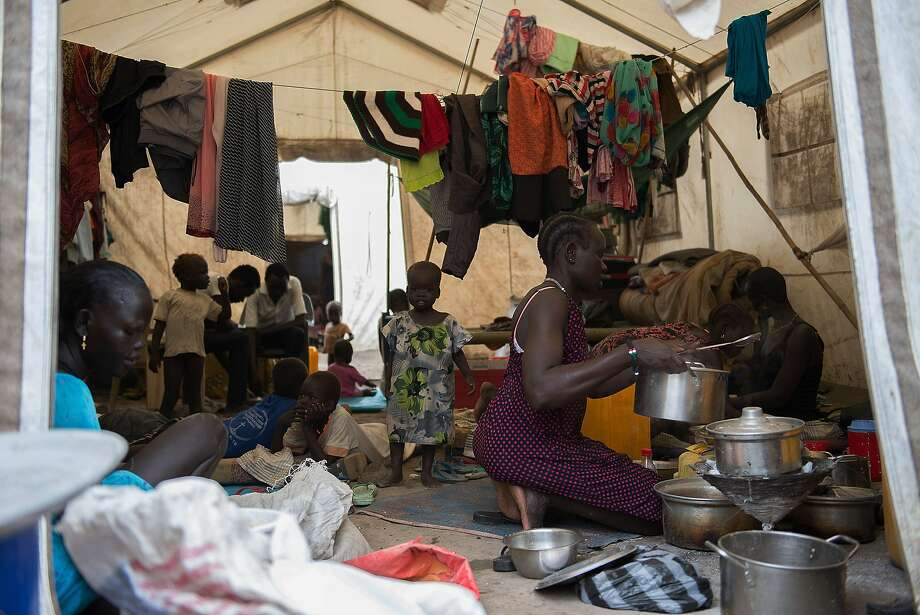 A woman prepares food at a refugee shelter in Juba, South Sudan, beset by violent civil conflict. Photo: Charles Lomodong, AFP/Getty Images