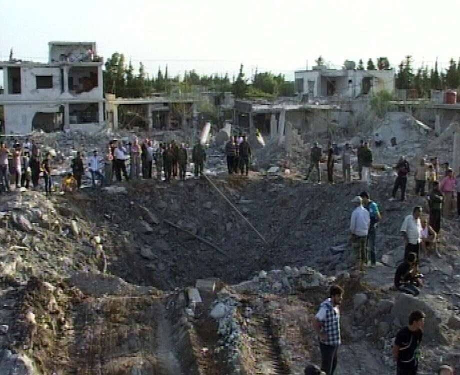 "TOPSHOTS A handout picture released by the official Syrian Arab News Agency (SANA) reportedly shows people gathering around a crater after a massive truck bomb killed at least 35 people in the government-controlled village of Al-Horra in the central Syrian province of Hama, on June 20, 2014. More than 50 people were wounded in the attack, SANA said, blaming the attack on rebels fighting to overthrow President Bashar al-Assad. AFP PHOTO/HO/SANA    == RESTRICTED TO EDITORIAL USE - MANDATORY CREDIT ""AFP PHOTO / HO / SANA"" - NO MARKETING NO ADVERTISING CAMPAIGNS - DISTRIBUTED AS A SERVICE TO CLIENTS ===-/AFP/Getty Images Photo: -, AFP/Getty Images"