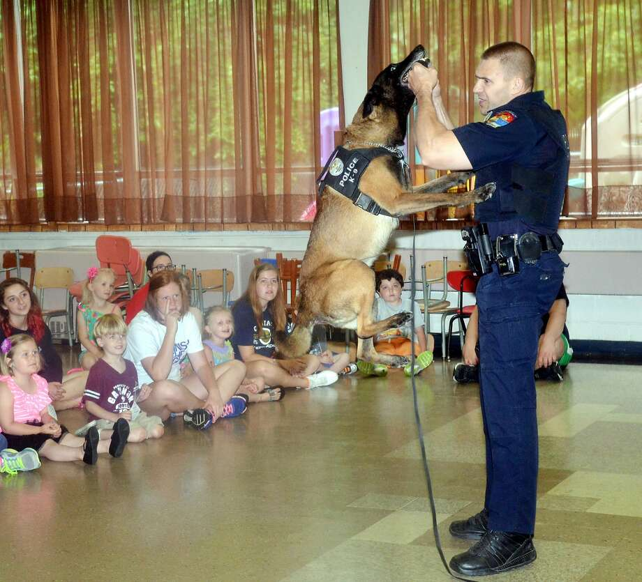 Friendly, tenacious Ghost:Officer Tim Rose conducts a demonstration with Ghost the police K-9 at a safety program in   Conneaut, Ohio. The photographer neglected to say what Ghost was demonstrating - how long he   can dangle by his jaws perhaps. Photo: Warren Dillaway, Associated Press