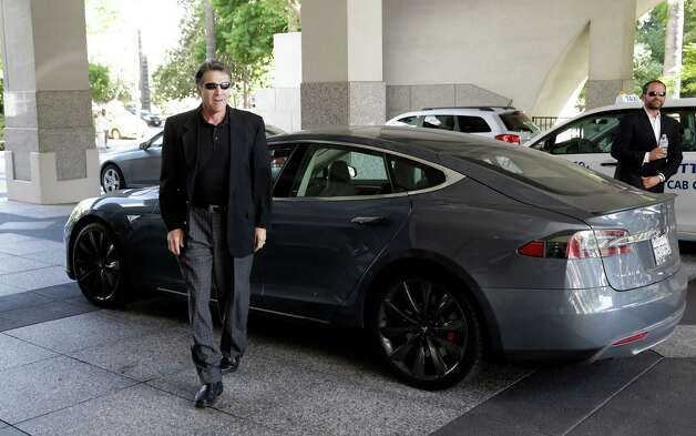 "File - In this June 10, 2014 file photo, Texas Gov. Rick Perry walks over to talk to reporters after driving up in a Tesla Motors Type S electric car in Sacramento, Calif. The Republican has made convincing top employers elsewhere to move to Texas a centerpiece of his administration. California has been a prime target, with Perry bashing what he calls the Golden State's high-tax, over-regulated ways. But a New York Times Magazine story released Tuesday says Perry told the reporter ""he loves California"" and ""might even move"" there in January, when his term ends. Photo: Rich Pedroncelli, AP / AP"