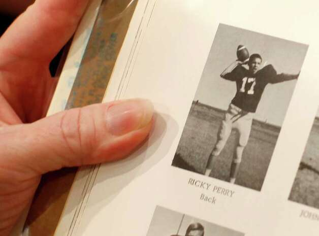 Becky Roe of Coal Valley, Ill., shows Republican presidential candidate Texas Gov. Rick Perry holding a football as a high school sophomore in the 1966 Paint Creek School yearbook while he makes a campaign stop at the Iowa 80 Group truck stop in Walcott, Iowa, Aug. 16, 2011. Roe, who lived in Paint Creek, Texas, was a third-grader when Perry was a high school sophomore. Photo: AP