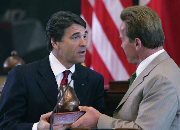 Texas Gov. Rick Perry accepts the gift of a statue of a California Bear from California Gov. Arnold Schwarzenegger during the closing ceremony of the border governors conference in the Texas Capitol, Aug. 25, 2006, in Austin. Photo: HARRY CABLUCK, AP / AP