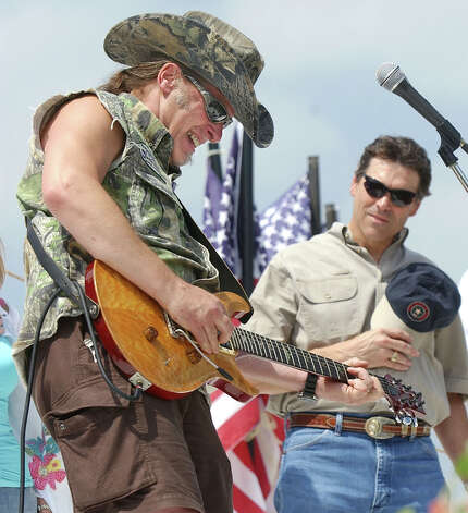 Ted Nugent plays an ear-splitting version of the Star Spangled Banner as Texas Gov. Rick Perry listens during the at the Bill Johnson ranch near Waco, June 4, 2005. As a way thank Fort Hood soldiers and their families for their service, Johnson hosted the event, called ''Operation Building Bridges.'' Photo: Duane A. Laverty/Waco Tribune-Herald/Associated Press