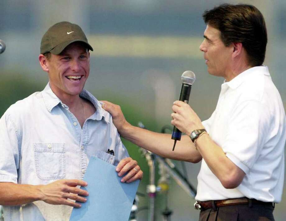 """Three-time Tour de France winner, Lance Armstrong accepts a proclamation from Texas Gov. Rick Perry during  a celebration dubbed """"Vive Lance! Austin's Hometown Hero,'' Aug. 4, 2001, in Austin. Photo: RALPH BARRERA, AP / AUSTIN AMERICAN STATESMAN"""