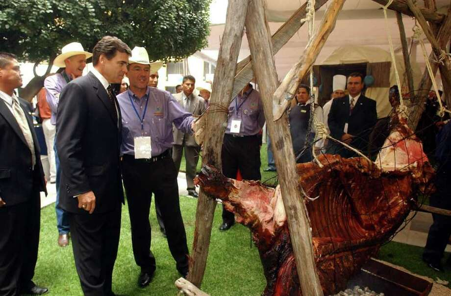Texas Governor Rick Perry checks out a side of beef with San Antonio Bid Committee member David Schmidt at the San Antonio luncheon at the Camino Real in Mexico City, Aug. 23, 2002. Photo: JERRY LARA, SAN ANTONIO EXPRESS-NEWS / SAN ANTONIO EXPRESS-NEWS
