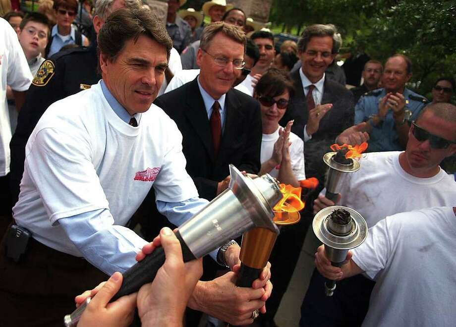 Texas Gov. Rick Perry lights a ceremonial torch outside the Capitol, May 1, 2006, as he takes part in a ceremony marking the 2006 Special Olympics.  Photo: RICARDO B. BRAZZIELL, AP / AUSTIN AMERICAN-STATESMAN