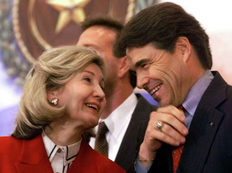 Texas Lt. Gov. Rick Perry laughs with Sen. Kay Bailey Hutchison, R-Texas, during a news conference in Austin, March 13, 2000. Photo: HARRY CABLUCK, AP / AP
