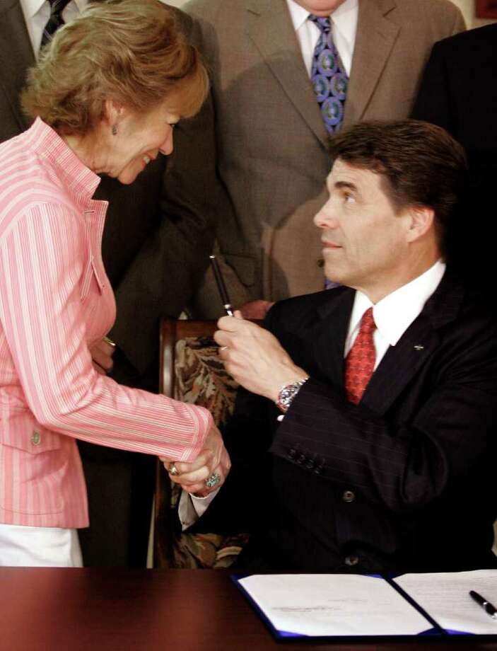 Texas Gov. Rick Perry presents the pen that he used for a ceremonial signing of the school finance bill in Irving, May 18, 2006, to Sen. Florence Shaparo, R-Plano. Photo: RON HEFLIN, AP / AP