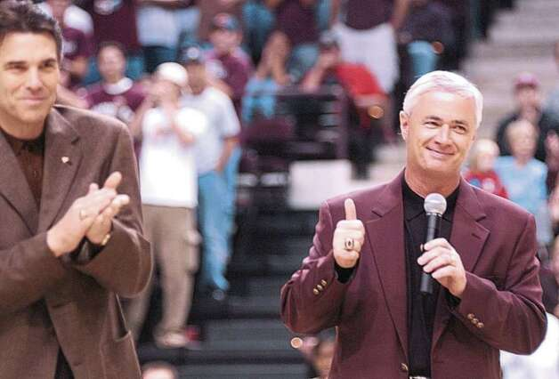 Texas Gov. Rick Perry applauds after introducing new Texas A&M football coach Dennis Franchione to the crowd before the start of the Texas A&M basketball game against Texas-San Antonio, Dec. 15, 2002, in College Station. Photo: DAVE MCDERMAND, AP / BRYAN EAGLE