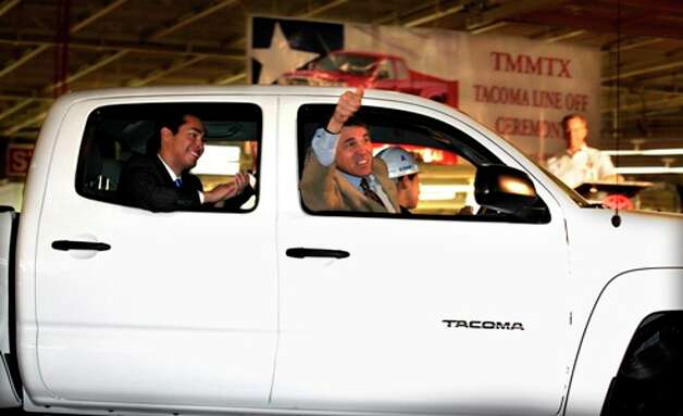Texas Gov. Rick Perry gives thumbs up as he and San Antonio Mayor Julian Castro (left) ride in the first Tacoma truck as Toyota holds its TMMTX Tacoma Line-Off Ceremony.