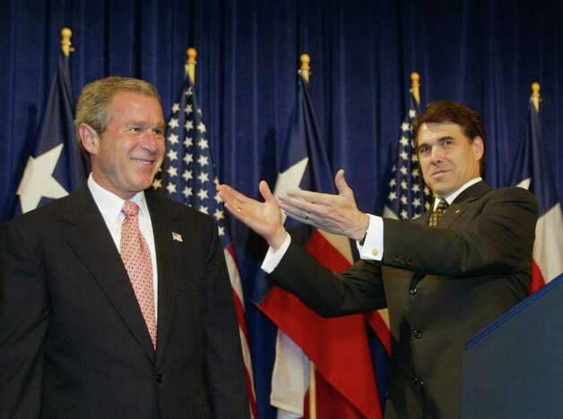 President George W. Bush receives a welcome from Texas Governor Rick Perry during 'Texans for Rick Perry' fundraiser, June 14, 2002, in Houston. Photo: RICK BOWMER, AP / AP