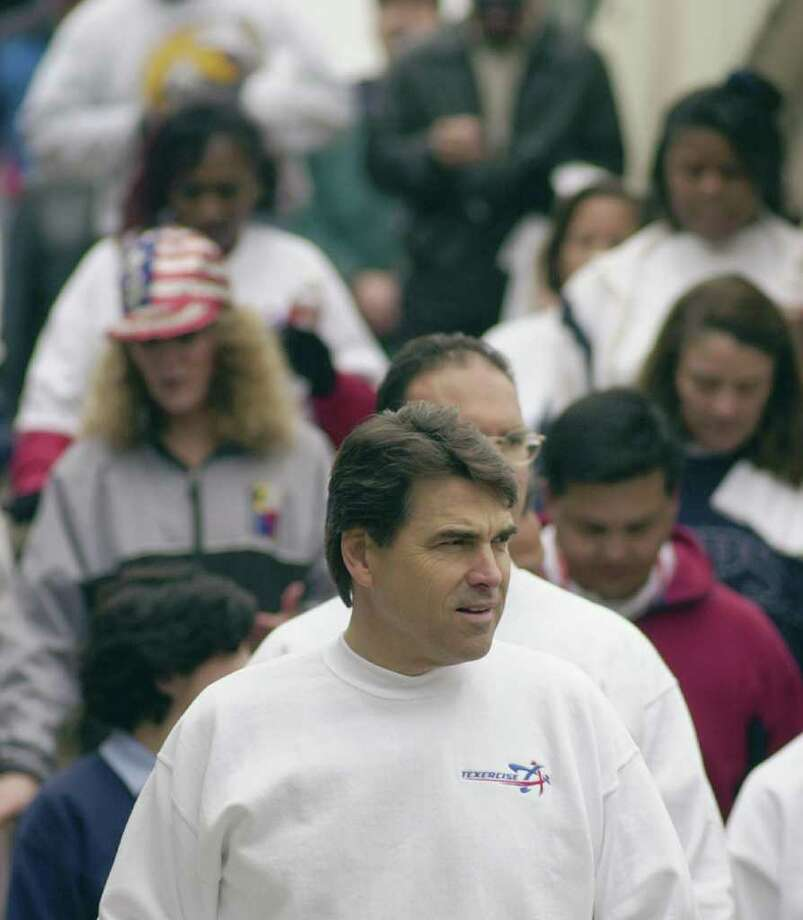Texas Gov. Rick Perry leads a pack during an afternoon fitness walk on a hike and bike trail, Jan. 18, 2002, in Austin. The walk marks the kickoff of the statewide Texercise initiative to promote physical fitness by the Texas Department of Aging. Photo: HARRY CABLUCK, AP / AP