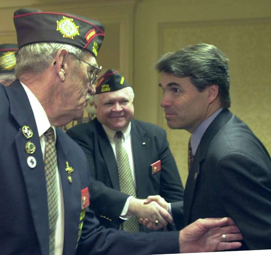 Texas Gov. Rick Perry listens to Troy Ellis (left) as he clasps the hand of Kenneth Burton after the governor's speech to the opening session of the Veterans of Foreign Wars conference, Jan. 25, 2002, in Austin. Photo: HARRY CABLUCK, AP / AP