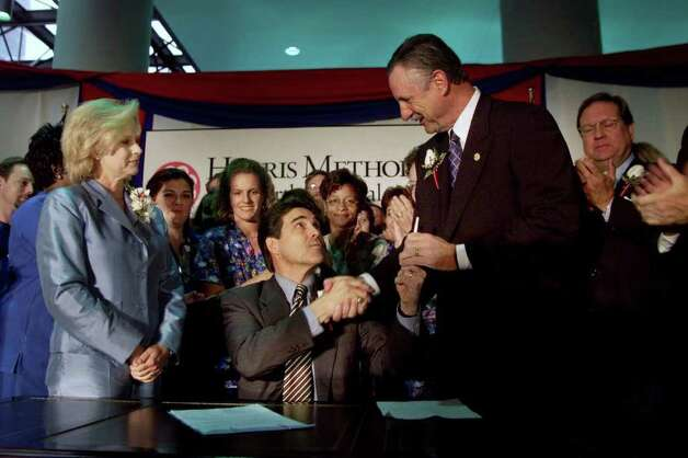 Texas Gov. Rick Perry shakes hands with Sen. Mike Moncrief, D-Fort Worth, after a signing of Senate Bill 572, Aug. 30, 2001,  that the governor and legislators hope will alleviate a shortage of nurses in the state by directing the state's higher education board to add more nursing education programs and to fund those programs in part with money from the tobacco settlement. At left is Texas first lady Anita Perry. Moncrief is the author of the bill. Both men credited the first lady, a former nurse, with lobbying for passage of the bill. The ceremony was held in the lobby of Harris Methodist Fort Worth Hospital. Photo: RODGER MALLISON, AP / FORT WORTH STAR-TELEGRAM