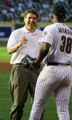 Texas Gov. Rick Perry smiles as he meets Houston Astros pitcher Mike Jackson after throwing out the first pitch in honor of Texas A&M University night, before the Astros' game against the Texas Rangers, June 15, 2001, in Houston. Photo: RICHARD CARSON, AP / AP