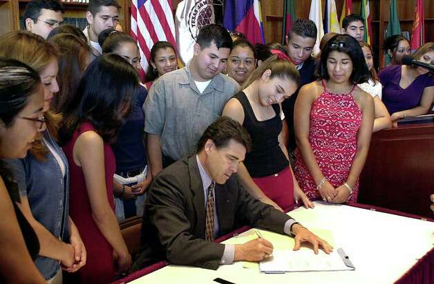 Texas Gov. Rick Perry is surrounded by Texas A&M International University students as he signs legislation creating the Texas Grant II program in Laredo, June 7, 2001. The legislation, proposed by Texas Secretary of State Dr. Henry Cuellar of Laredo, when he was a state representative, makes college more afforable and more accessible to a greater number of Texans. All the students surrounding Gov. Perry are recipients of the Texas Grant. Photo: RICARDO SANTOS, AP / LAREDO MORNING TIMES