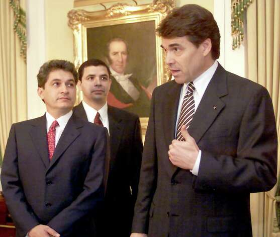 Texas Governor Rick Perry answers questions following a news conference held with Tomas Yarrington, governor of the Mexican state of Tamaulipas (left) and Texas Secretary of State Henry Cuellar (center) at the Governor's Mansion in Austin, Feb. 22, 2001, where the governors discussed boosting cross-border trade. Photo: DEBORAH CANNON, AP / AP