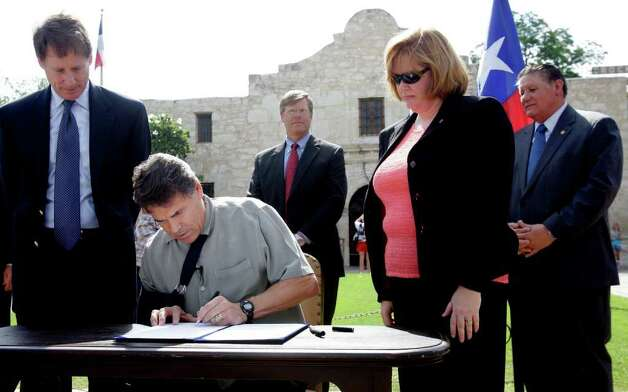 Rick Perry used the Alamo as a backdrop for signing a bill that asked voters to place limits on when the government can take land using its eminent domain authority. Photo: Eric Gay, Associated Press / AP
