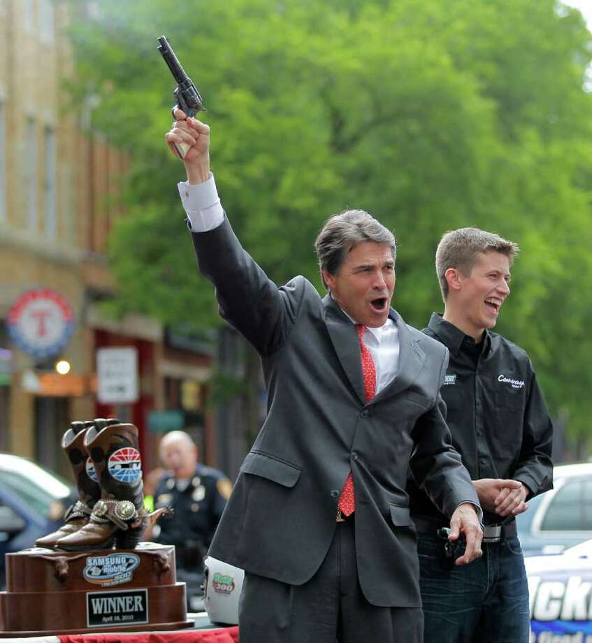 Texas Governor Rick Perry has some fun with a pistol filled with blanks as NASCAR driver Colin Braun looks on at an event in downtown Fort Worth to kickoff a weekend of NASCAR racing at the Texas Motor Speedway, April 15, 2010. Photo: AP