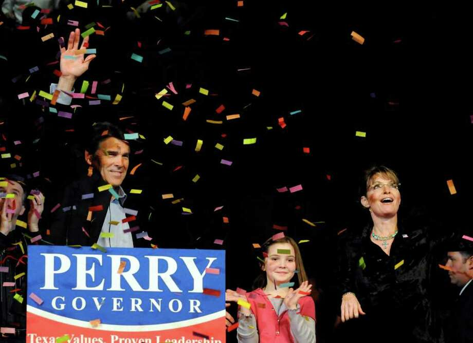 Texas Gov. Rick Perry, left, and former Alaska Gov. Sarah Palin with her daughter Piper wave to the crowd as the confetti falls at a Perry campaign rally, Feb. 7, 2010 in Cypress. Photo: AP