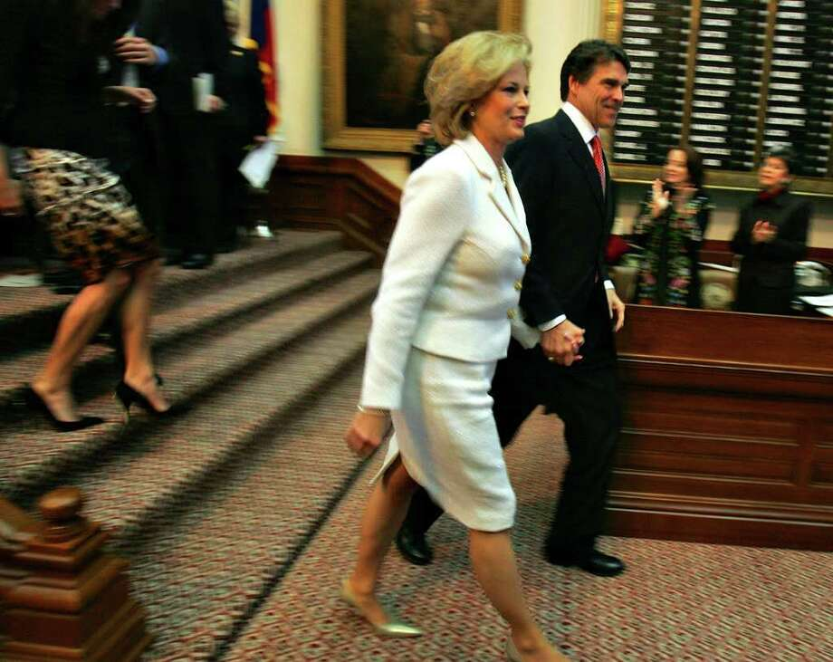 Gov. Rick Perry and his wife Anita leave the floor of the House Chamber after Perry took the oath of office, Jan. 16, 2007 at the Capitol in Austin. The ceremony was moved inside the Capitol building due to bad weather.  Photo: BAHRAM MARK SOBHANI, SAN ANTONIO EXPRESS NEWS / SAN ANTONIO EXPRESS NEWS