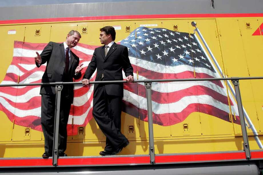 Gov. Rick Perry was in town at the Union Pacific South San Antonio Rail Yard to sign an agreement with Union Pacific CEO Dick Davidson intended to reduce the amount of  rail freight traffic through urban areas. HDavidson gave the governor a tour of a locomotive.  Photo: J. MICHAEL SHORT, SPECIAL TO THE EXPRESS-NEWS / THE SAN ANTONIO EXPRESS-NEWS