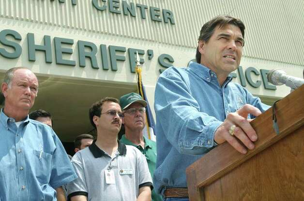 With Comal County and New Braunfels officials behind him, Gov. Rick Perry reveals his grim observations of flooding devastation, July 7, 2002.  Perry had just completed a helicopter tour of the area around Canyon Lake. Photo: TOM REEL , SAN ANTONIO EXPRESS-NEWS / SAN ANTONIO EXPRESS-NEWS