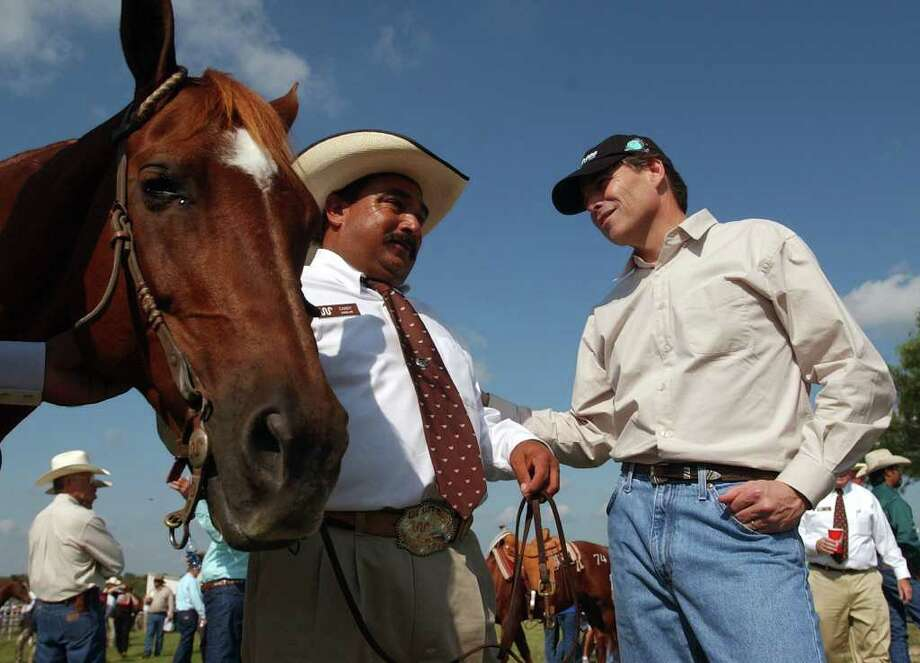 Gov. Rick Perry, right, talks with Candy Aguilar, Oct. 4, 2003, before the start of the King Ranch 150th Anniversary Legacy Sale on the Santa Gertudis Division of the ranch. The rare auction was held to celebrate the 150th Anniversary of the founding of the ranch. Photo: WILLIAM LUTHER, SAN ANTONIO EXPRESS-NEWS / SAN ANTONIO EXPRESS-NEWS