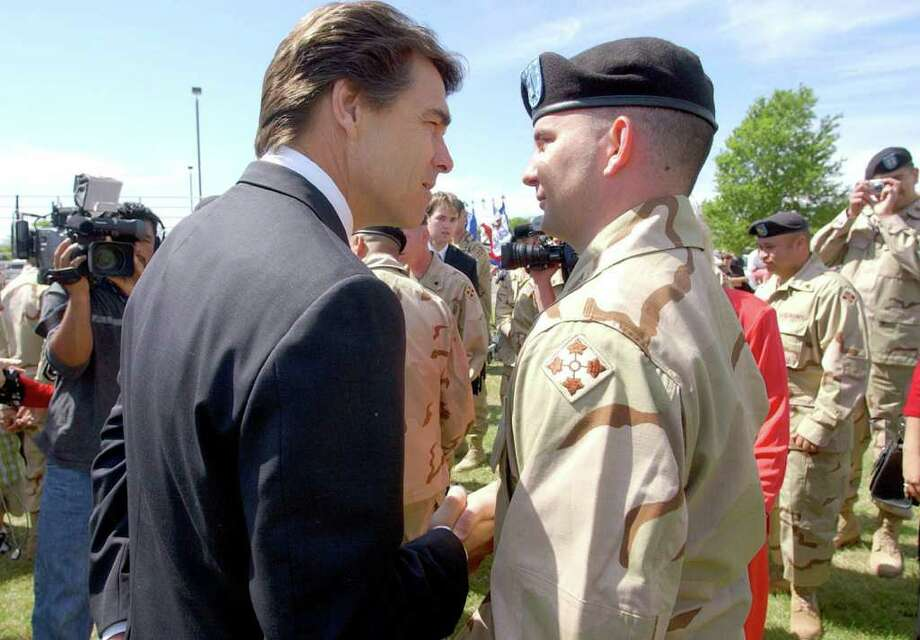 Gov. Rick Perry wishes Army Warrant Officer Taylor Petty of San Antonio well at farewell ceremonies at Fort Hood for the 4th Infantry Division. The troops there were shipping out to the Middle East because of the war in Iraq.  Photo: JOHN DAVENPORT, SAN ANTONIO EXPRESS-NEWS / SAN ANTONIO EXPRESS-NEWS