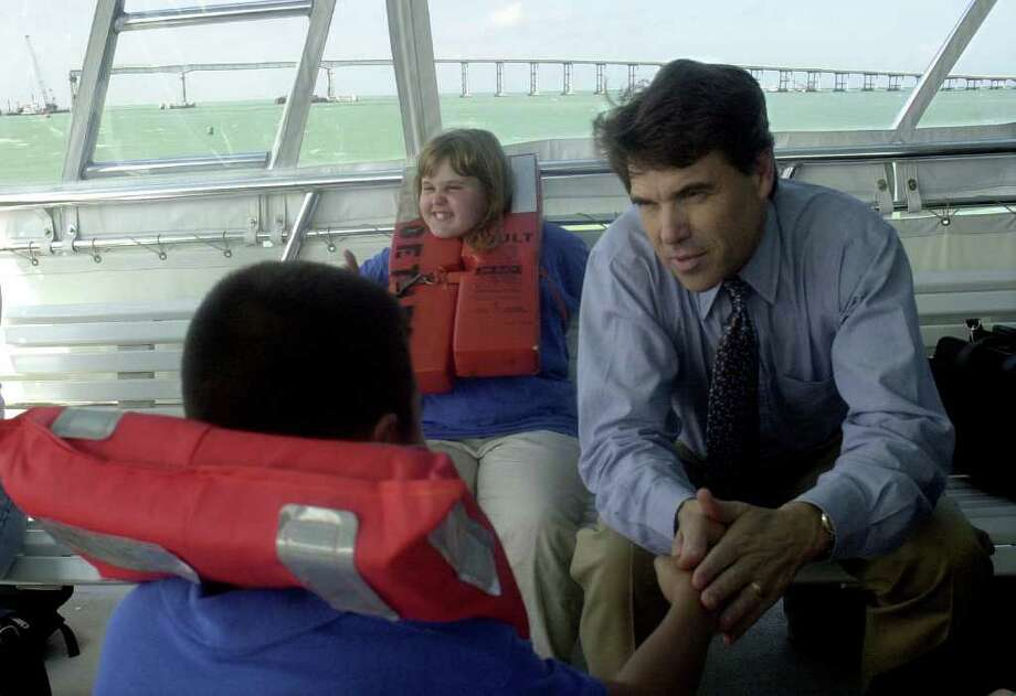 Gov. Rick Perry speaks to Jesus Recendiz, 9, a third-grader from Derry Elementary School in Port Isabel as the youngster and his classmates commute across the Laguna Madre to their hometown of South Padre Island, Oct. 10, 2001. Students who live on the island have to commute to school via ferry boat since the partial collapse of the Queen Isabella Causeway, shown in the background. To the right of the governor is Lyndsey Nebben, 11.  Photo: Alicia Wagner Calzada, Freelance
